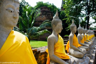 Buddhas lined up in a roll in a temple in Ayutthaya Thailand