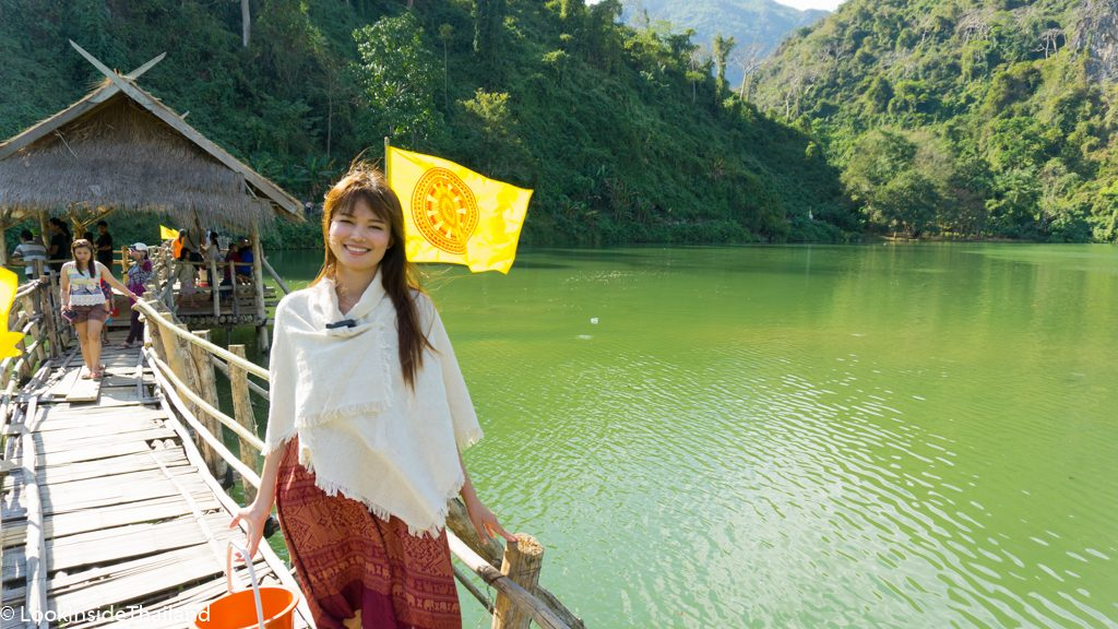 Green emerald lake with wooden bridge